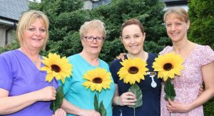 SUPPORT: Volunteers for the North West Hospice Sunflower Days show off some of the sunflowers and pins which will be for sale from June 9-11.Caption